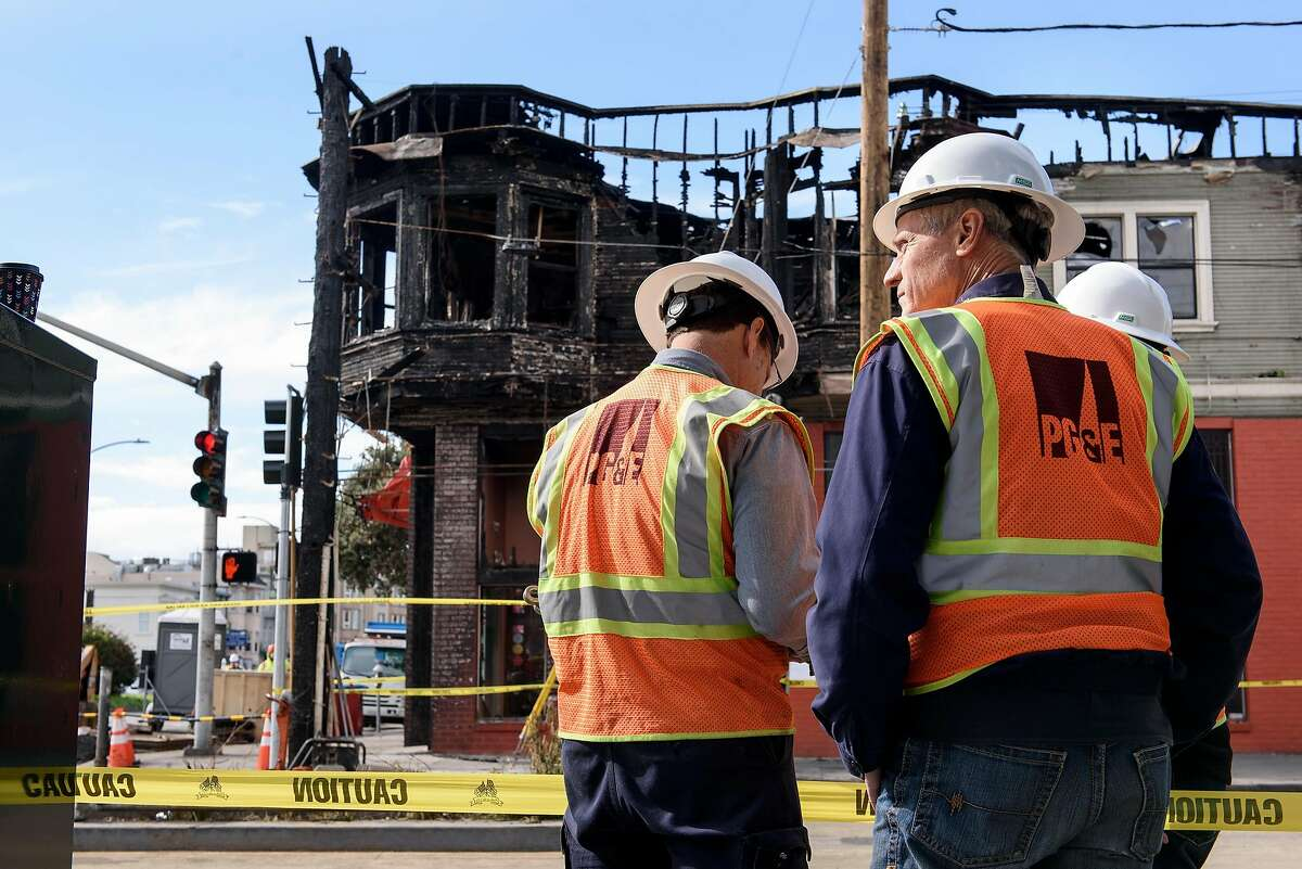 A group of PG&E workers stand in front of the burnt out Hong Kong Lounge II restaurant which was the site of a gas fire caused when contractors installing fiber optic cable hit a PG&E pipeline, in San Francisco, Calif., on Thursday, February 7, 2019.