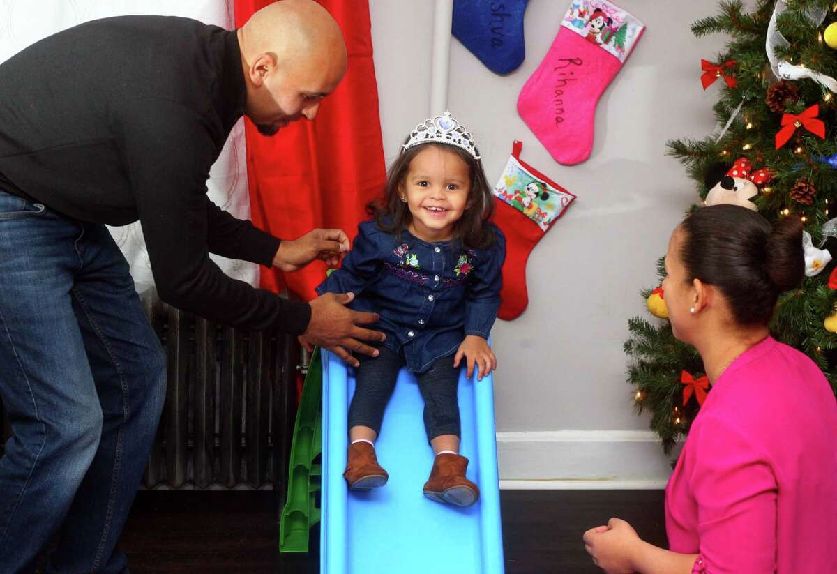Ana and Enrique Plaza play with their 2-year-old daughter, Rihanna, at their home in the East End neighborhood of Bridgeport, Conn., on Dec. 12, 2018. Rihanna was one of the first patients in the world to take Larotrectinib, a cancer drug made by Stamford-based Loxo Oncology and approved Nov. 26, 2018 by the U.S. Food and Drug Administration.