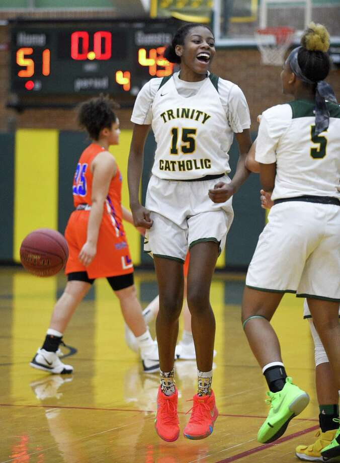 Trinity Catholic's Iyanna Lops (15) celebrates with Kyah Nowlin (5) following the Crusaders 51-43 win over the Danbury Hatters in an FCIAC girls high school basketball game in Stamford, Conn. on Friday, Feb. 8, 2019. Lops scored her 1000th career point in the first half of the game. Photo: Matthew Brown / Hearst Connecticut Media / Stamford Advocate