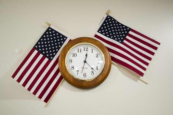 American flags are wedged behind a wall clock inside Fire Station 1 on Nov. 15, 2018 in Midland. (Katy Kildee/kkildee@mdn.net)