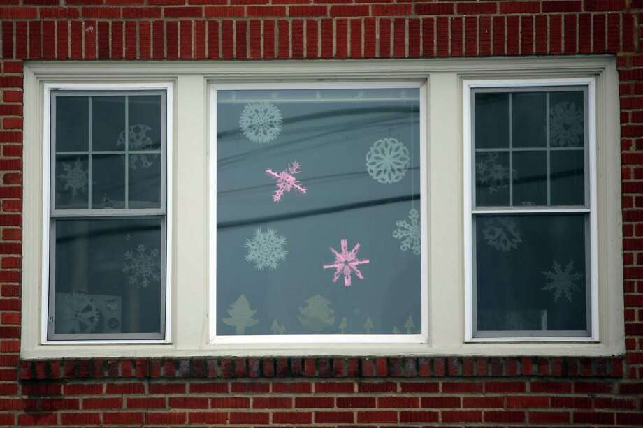 Paper snowflakes hang in a window at Alki Beach as snow falls Friday afternoon in West Seattle, beginning what is expected to be a heavy storm that continues into Saturday and brings several inches of snow to Seattle, Jan. 8, 2019. Photo: Genna Martin, Seattlepi.com / SeattlePI