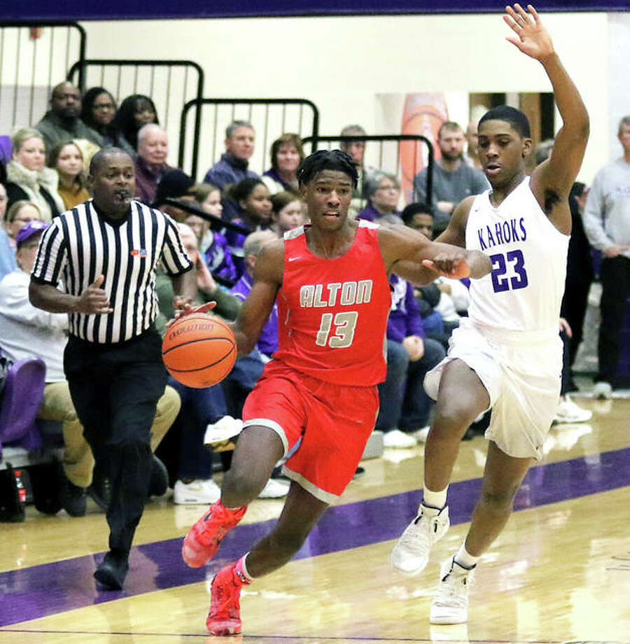Alton's Malik Smith (13) pushes past midcourt while Collinsville's Marshall Harrison pursues the play Friday night in a SWC boys basketball game at Fletcher Gym in Collinsville. Photo: Greg Shashack | The Telegraph