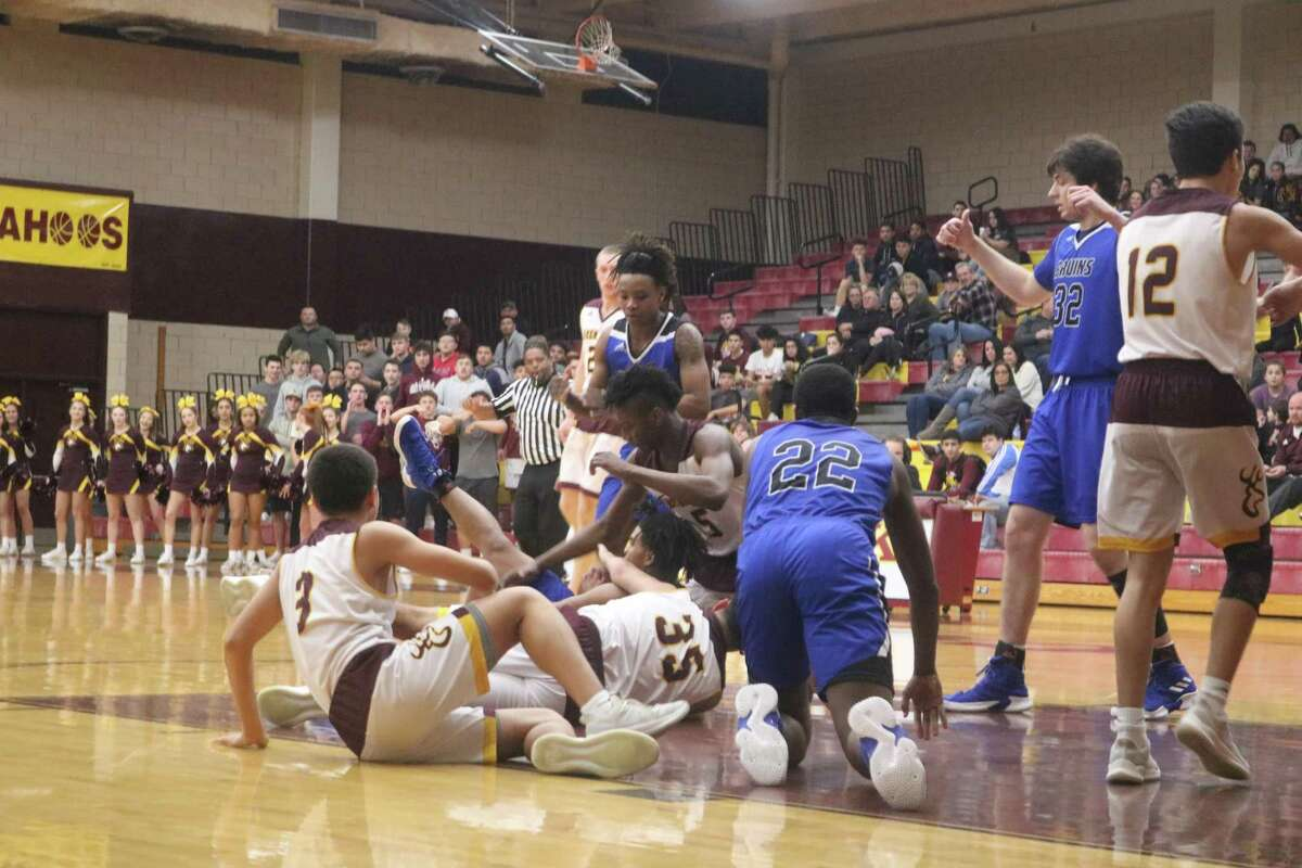 Somewhere in there is a basketball as Deer Park and West Brook players vie for control of a loose ball Friday night.