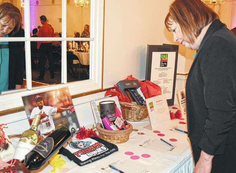 Leanna Wynn of Jacksonville looks at items up for bid Friday at the Jacksonville Rotary Club Foundation One Love Gala.