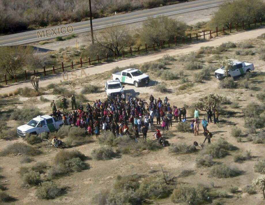 Authorities apprehend migrants Thursday after they illegally crossed the U.S.-Mexico border near Lukeville, Ariz., in an image released by the Customs and Border Protection agency. Photo: Customs And Border Protection