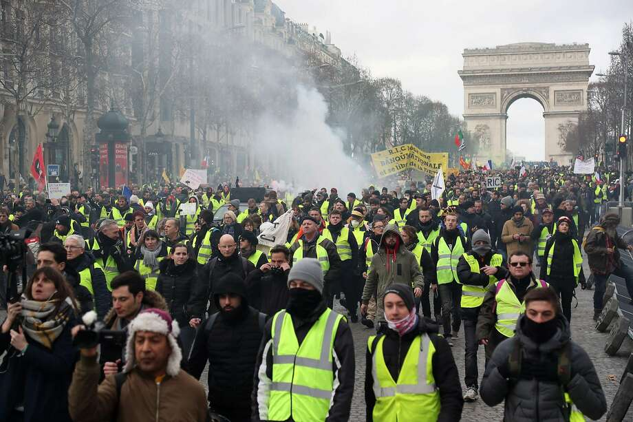 Protesters march near the Arc de Triomphe in Paris in the 13th consecutive Saturday that rallies have been held. Photo: Zakaria Abdelkafi / AFP / Getty Images