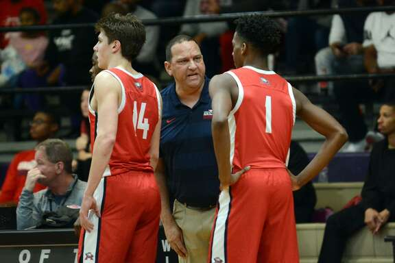 Atascocita Head Boys Basketball Coach David Martinez, center, pumps up sophomore guard Justin Collins (1) during a change of posession.