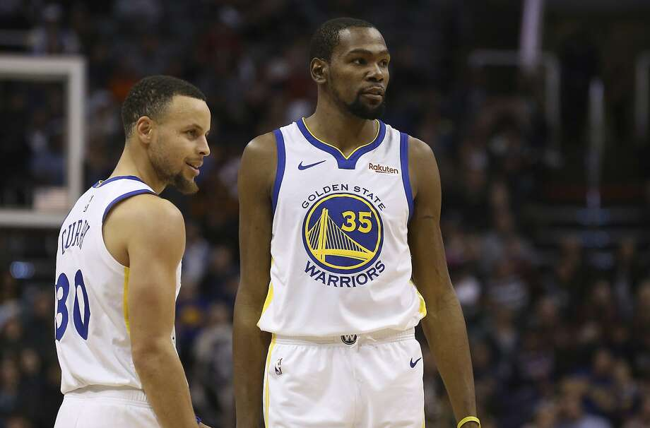Golden State Warriors guard Stephen Curry (30) and forward Kevin Durant (35) pause during the first half of an NBA basketball game against the Phoenix Suns Friday, Feb. 8, 2019, in Phoenix. The Warriors defeated the Suns 117-107. (AP Photo/Ross D. Franklin) Photo: Ross D. Franklin / Associated Press