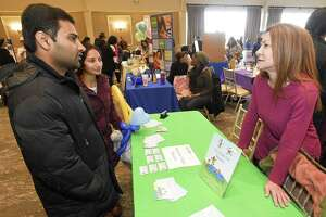 Debbie Eposito , at right, speaks with Satwik Dasaram of Stamford and his wife Prathyusha Kottireddy about childcare services during the 11th Annual 2019 Stamford Early Childhood Fair on Saturday, Feb. 2, 2019 in Stamford, Connecticut. Eposito, a family child care provider who is unable to hire help due to changes in Connecticut Child Care legislation and delays in state background and fingerprinting checks, runs Beginner Steps daycare out of her home in Stamford.