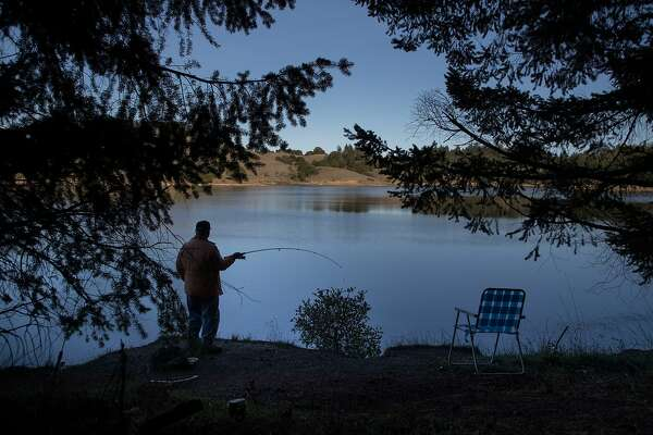 Tom Bujakowski brings a lawn chair to fish for trout at Bon Tempe Lake on Friday, Dec. 28, 2018, in Marin County, Calif.