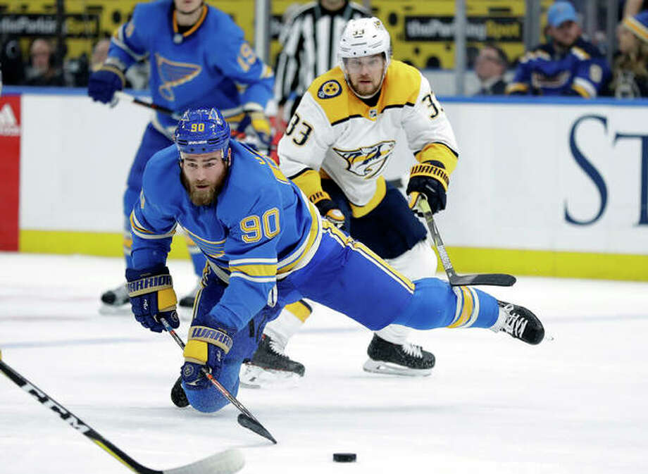 The Blues' Ryan O'Reilly (90) reaches for a loose puck as the Predators' Viktor Arvidsson (33) follows the play Saturday in St. Louis. Photo: Associated Press