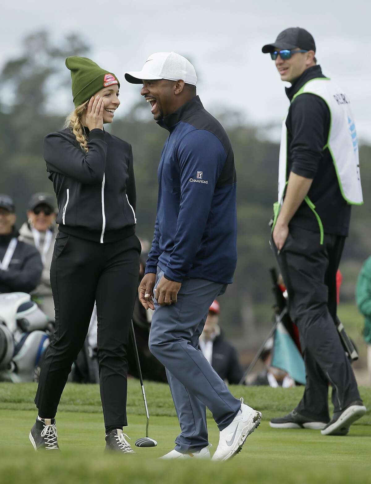 Alfonso Ribeiro, center and Kira Kazantsev, left, laugh after putting on the sixth green of the Pebble Beach Golf Links during the third round of the AT&T Pebble Beach Pro-Am golf tournament, Saturday, Feb. 9, 2019, in Pebble Beach, Calif. (AP Photo/Eric Risberg)