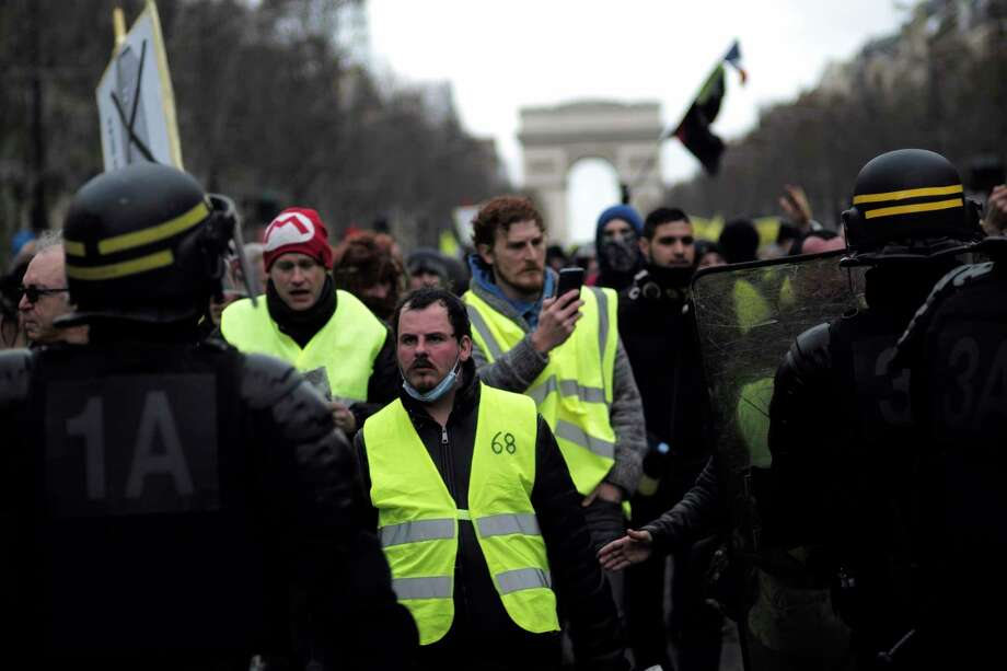 Yellow vest protesters walk down the famed Champs Elysees avenue to keep pressure on French President Emmanuel Macron's government, for the 13th straight weekend of demonstrations, in Paris, France, Saturday, Feb. 9, 2019. (AP Photo/Kamil Zihnioglu) Photo: Kamil Zihnioglu / Copyright 2019 The Associated Press. All rights reserved.