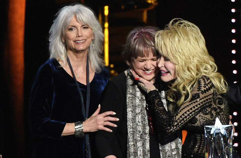 Emmylou Harris, from left, and Linda Ronstadt present Dolly Parton with the MusiCares Person of the Year award on Friday, Feb. 8, 2018, at the Los Angeles Convention Center. (Photo by Chris Pizzello/Invision/AP) Photo: Chris Pizzello / Invision