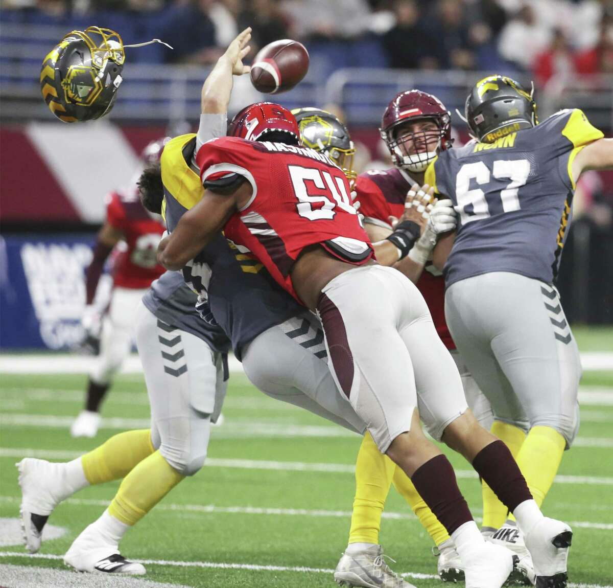 San Antonio linebacker Shaan Washinton knocks the helmet off of the Fleet quarterback Mike Bercovici as the Commanders host San Diego at the Alamodome in the opening game for the Alliance of American Football league on February 9, 2019.