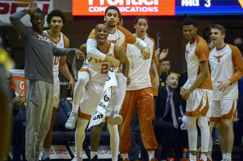 Texas players react after another slam dunk by teammate Jericho Sims (20) during the second half of an NCAA college basketball game against West Virginia in Morgantown, W.Va., Saturday Feb. 9, 2019. (AP Photo/Craig Hudson) Photo: Craig Hudson/Associated Press