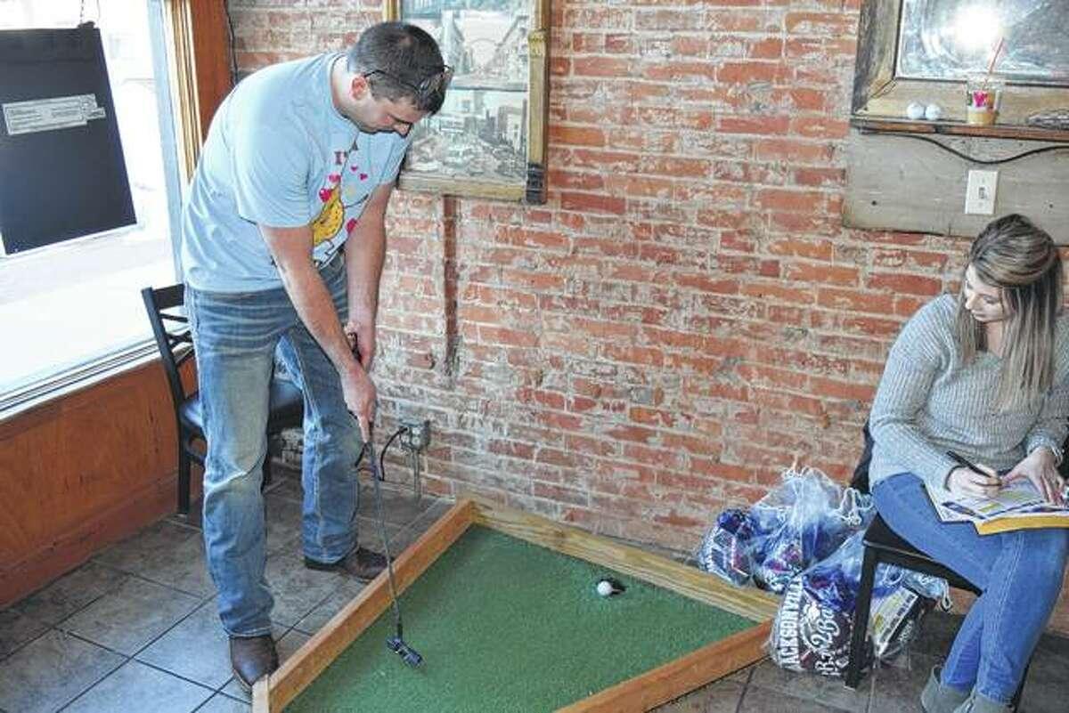 Tom Reynolds sinks a putt Saturday at Brickhouse BBQ for the 18th annual Bar 2 Bar