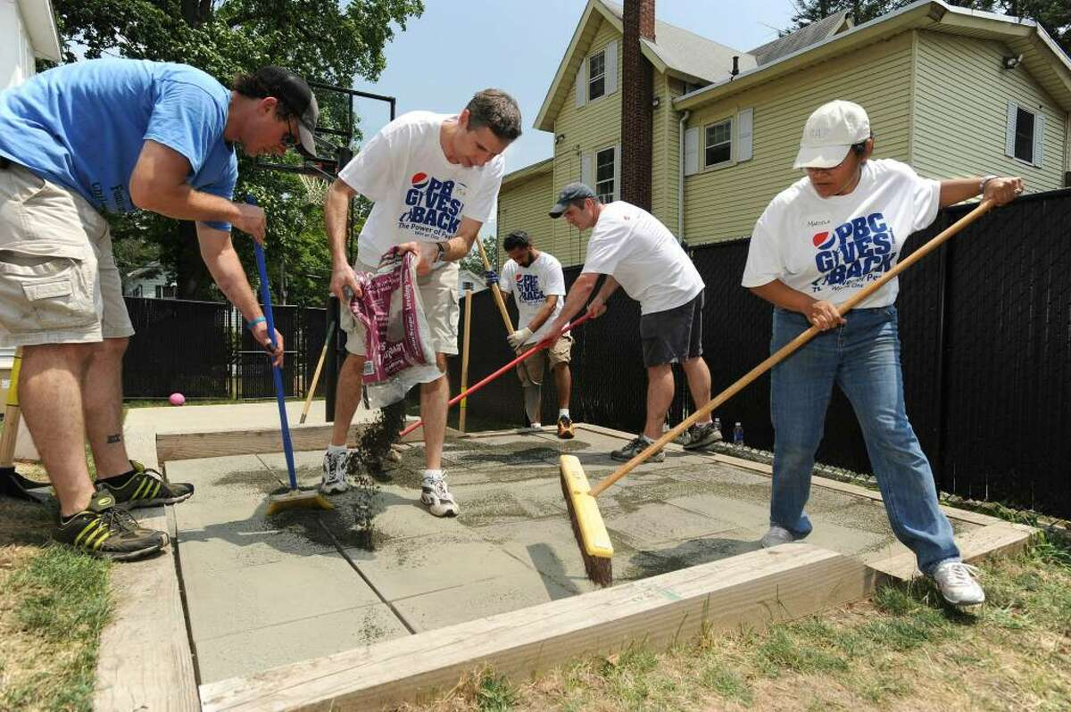 Pepsico volunteers lay down a patio. From left: Nick Hoffman, family and children's Aid with Pepsi volunteers: Bob Spear, Jas Gulati, Andrew Bradley and Marcela Ventura-Diaz.