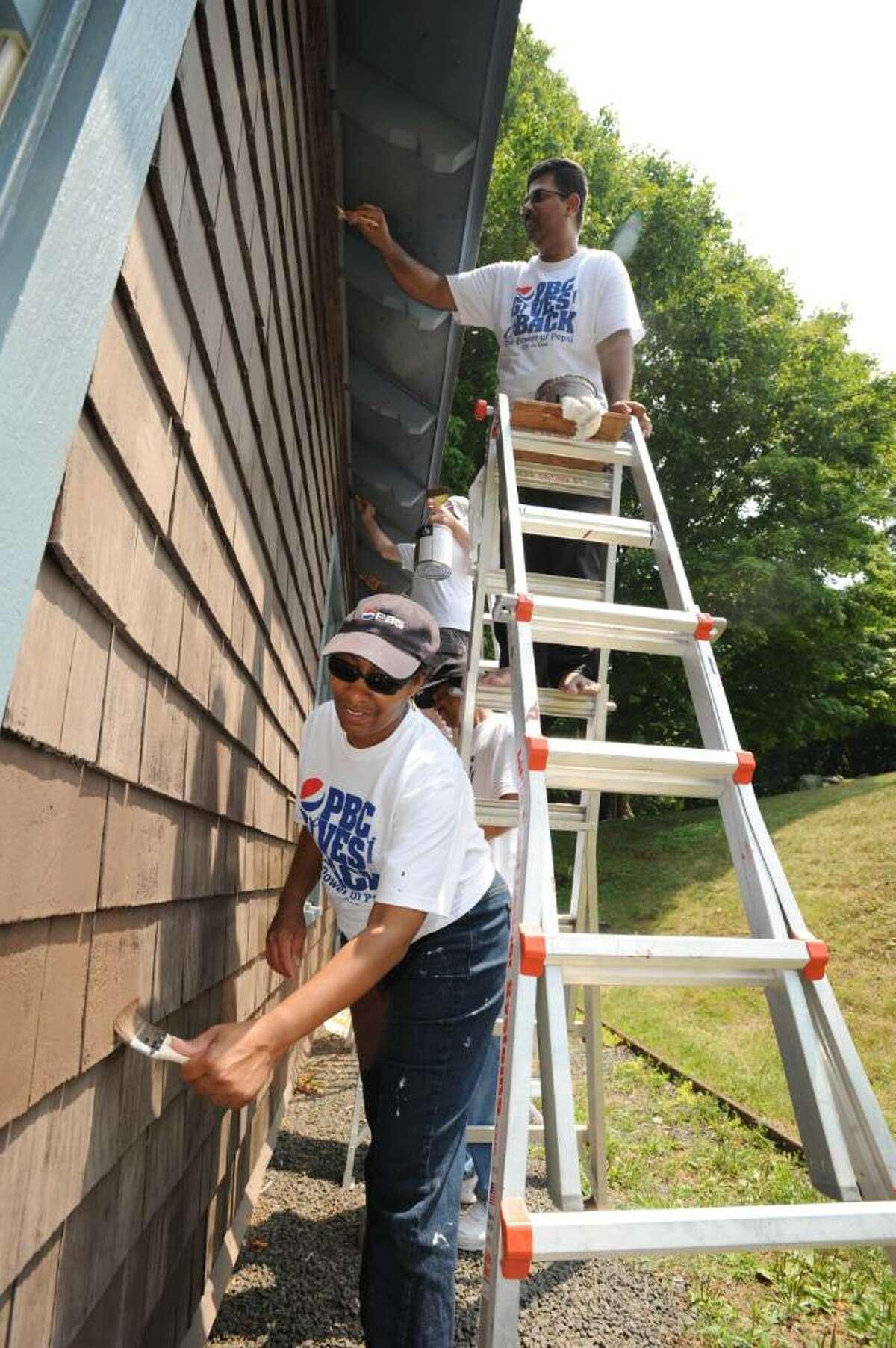Pepsi volunteers Kenita Hickman-Johnson, left, and Vijay Rao paint at the Tarrywile Park Authority.