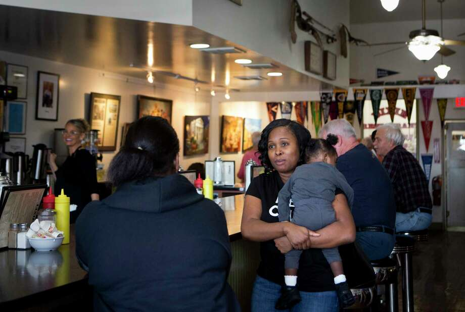 "Jackie Branch holds granddaughter Madison Parham at the Dixie Restaurant on Friday in Petersburg, Va. ""Everybody has a past,"" she said of Gov. Ralph Northam, alluding to the revelation of a racist photo on his medical school yearbook page. Photo: Photo For The Washington Post By Julia Rendleman / Julia Rendleman"