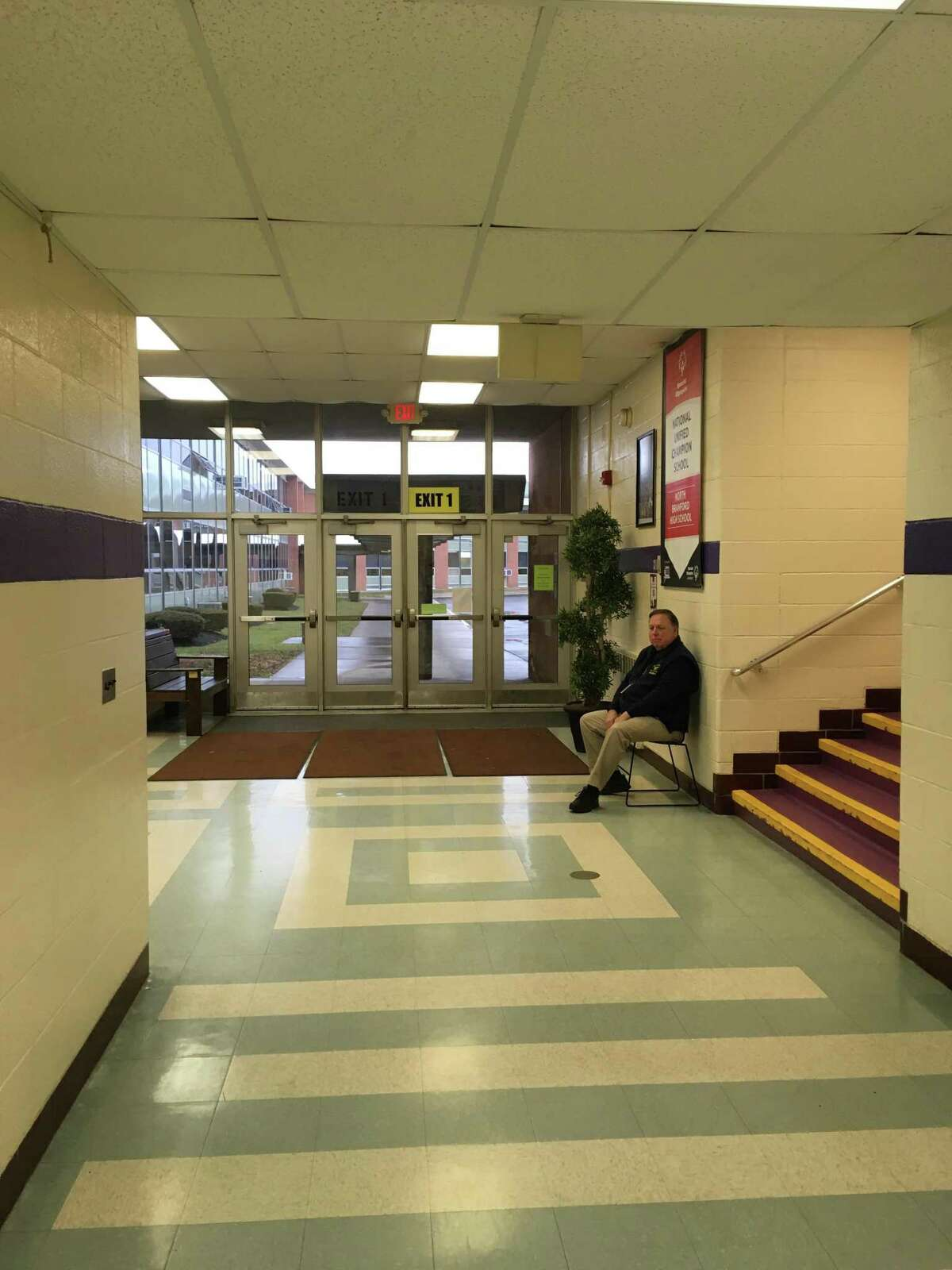A security guard sits inside of the main entrance to North Branford High School, Feb. 8, 2019.