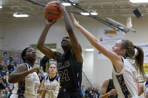 Willis forward De'Janae Gilmore (21) shoots under pressure during the first quarter of a District 20-5A high school playoff play-in game at Conroe High School, Friday, Feb. 8, 2019, in Conroe.