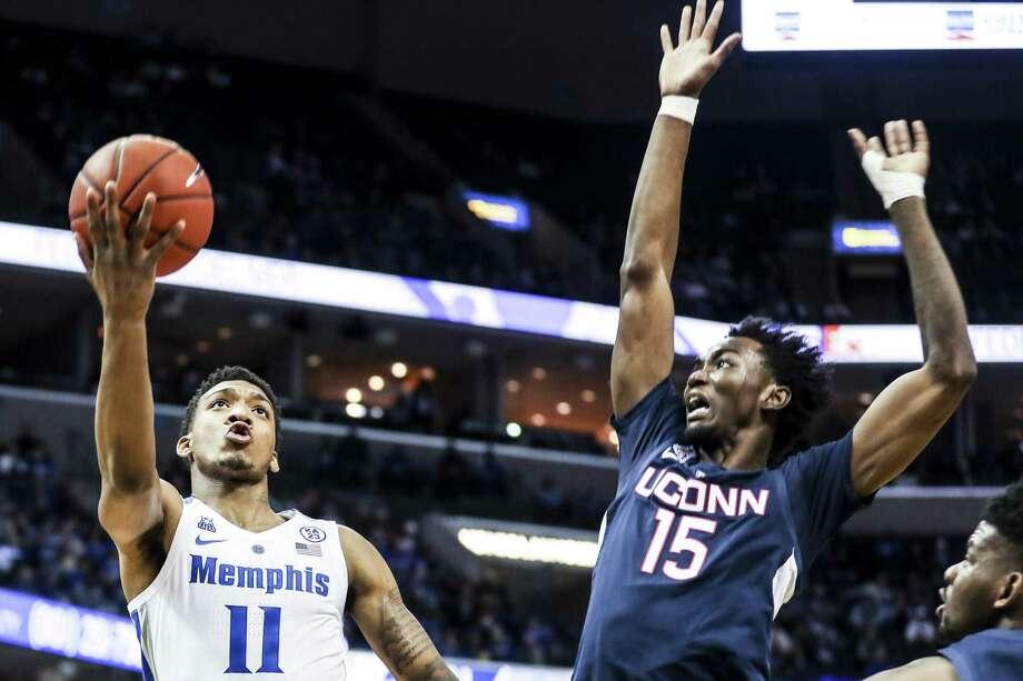 UConn's Sidney Wilson, right, attempts to block a shot by Memphis' Antwann Jones on Sunday. Photo: Brad Vest / Associated Press / Brad Vest