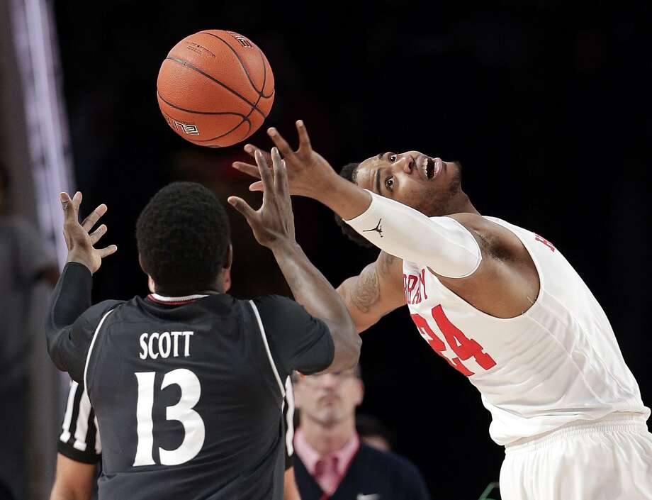 Cincinnati forward Trevon Scott (13) and Houston forward Breaon Brady (24) reach for a rebound during the first half of an NCAA college basketball game Sunday in Houston. Photo: Michael Wyke, FRE / Associated Press / Copyright 2019 The Associated Press. All rights reserved.