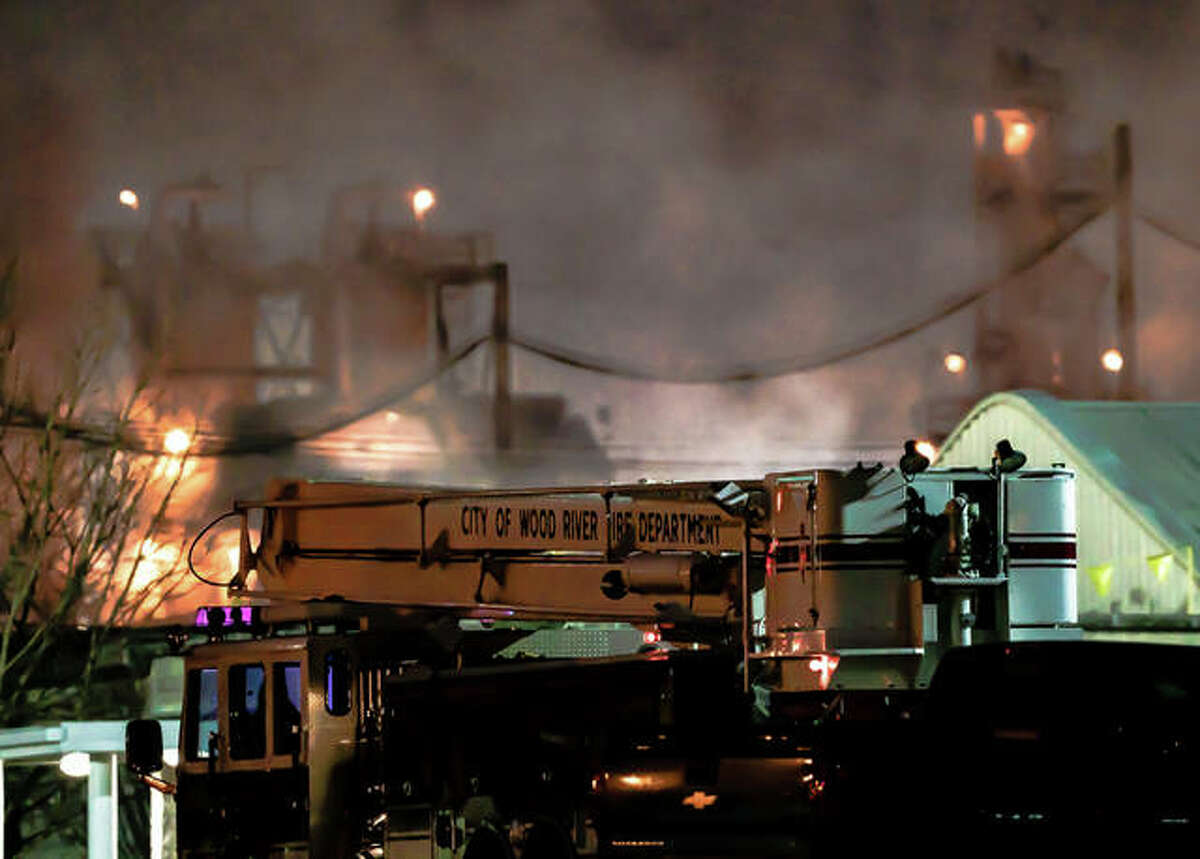 Police and fire crews assist the Wood River Phillips 66 refinery's emergency response team Sunday evening after a fire and explosion left an employee injured.