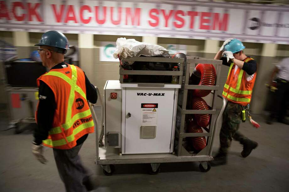 Rail workers move a prototype vacuum system out of a work area at the Jamaica Center - Parsons/Archer station in New York, June 29, 2017. The Metropolitan Transportation Authority are testing battery-powered vacuums to clean up the trash that riders leave behind, which can catch fire and create delays. (Kevin Hagen/The New York Times) ORG XMIT: XNYT72 Photo: KEVIN HAGEN / NYTNS