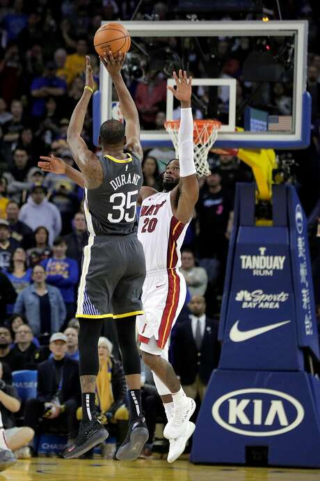The Warriors' Kevin Durant shoots over Miami's Justise Winslow to tie the game at 118. Photo: Carlos Avila Gonzalez / The Chronicle