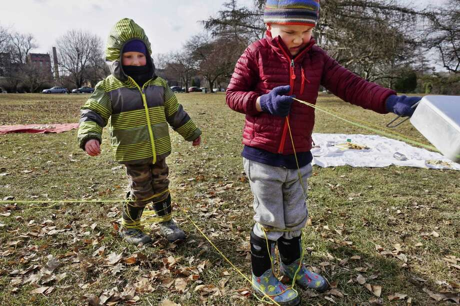 "Sean O'Brien, 4, left, of Brunswick waits for some help from Ben Larrabee, 4, of Glenmont, as Larrabee uses a metal pan to try and cut through the yarn he and O'Brien wrapped themselves up in at the Albany Pop-Up Adventure Playground at Washington Park on Sunday, Feb. 10, 2019, in Albany, N.Y. The pop-up was started by Moira Mills who ran five of them this past summer. ""The first pop-up had 20 people and by the fifth one we had 120 people at the pop-up"", Mills said. The pop-up is open to children from 0-11 years old, and is filled with loose parts, things that do not have a singular purpose. Parents are encouraged to stay out of the way and let the kids play amongst themselves and to let their kids get dirty. Mills is in the process of planning this summer's pop-ups which she believes will run between May and October. Mills is the owner of Rebl Mom, a business where she works with parents of boys to help them embrace the rambunctiousness of boyhood in a world that may not. Parents looking for information on the next pop-up playground can search for Albany Pop-up Adventure Playground on Facebook.  (Paul Buckowski/Times Union) Photo: Paul Buckowski / (Paul Buckowski/Times Union)"