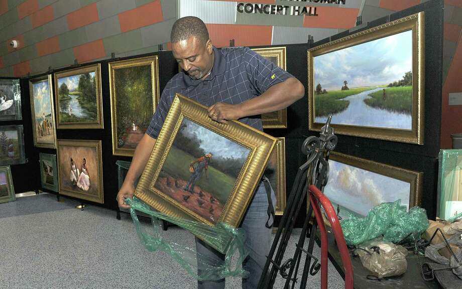 Artist Ted Ellis will be featured along with his artwork at the Feb. 13 Black History Monty Celebration hosted by Missouri City at the Visitors Center, 1522 Texas Parkway. Ellis, above, arranges a display of his work in the lobby of Western Connecticut State University's Visual and Performing Arts Center in September 2018. Photo: Carol Kaliff, Photo Editor / Hearst Connecticut Media / The News-Times