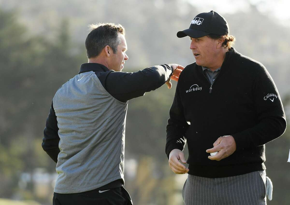 PEBBLE BEACH, CALIFORNIA - FEBRUARY 11: Paul Casey of England pats Phil Mickelson of the United States on the back on the 18th green during the continuation of the final round of the AT&T Pebble Beach Pro-Am at Pebble Beach Golf Links on February 11, 2019 in Pebble Beach, California. (Photo by Harry How/Getty Images)