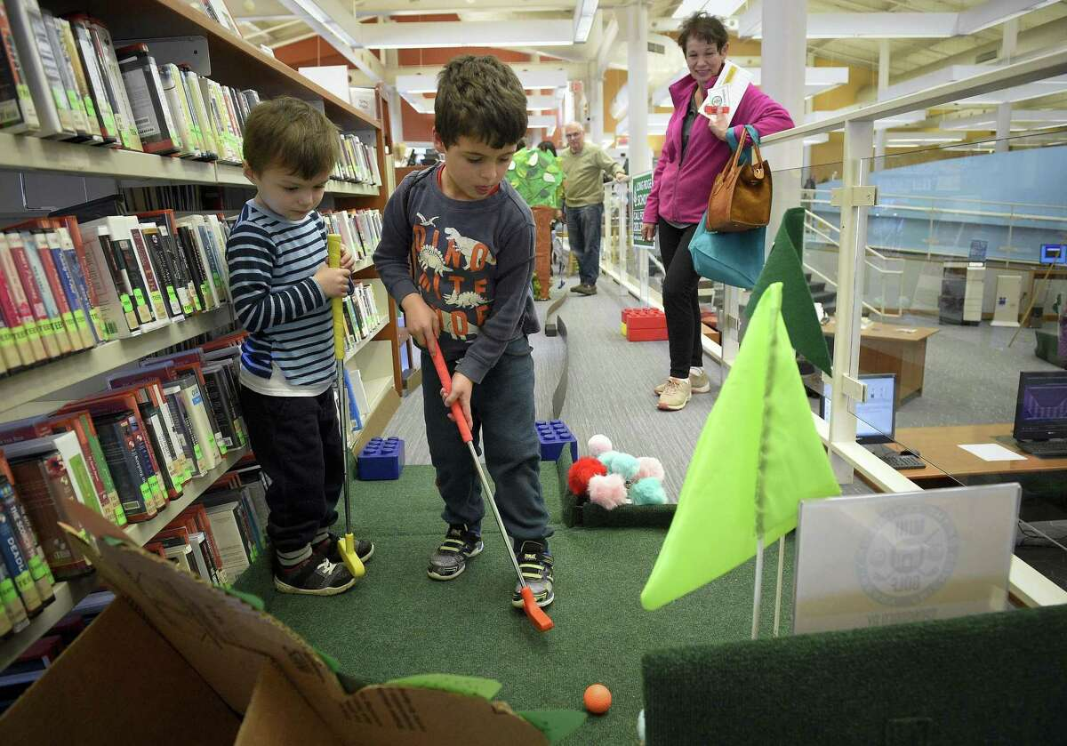 Janice Corsello of Trumbull watches her grandsons, from left, JJ Wasowski, 3 and his cousin Edward Corsello, 4, play a round of mini-golf during a fundraising event at the Harry Bennett Branch of the Ferguson Library on Saturday, Feb. 9, 2019 in Stamford, Connecticut.