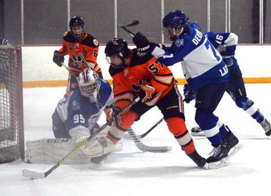 Edwardsville's Justin Harper, middle, tries to put the puck past Ladue goalie Mac Beatrice during the third period of a Jan. 31 playoff game at the East Alton Ice Arena. Photo: Scott Marion/Intelligencer