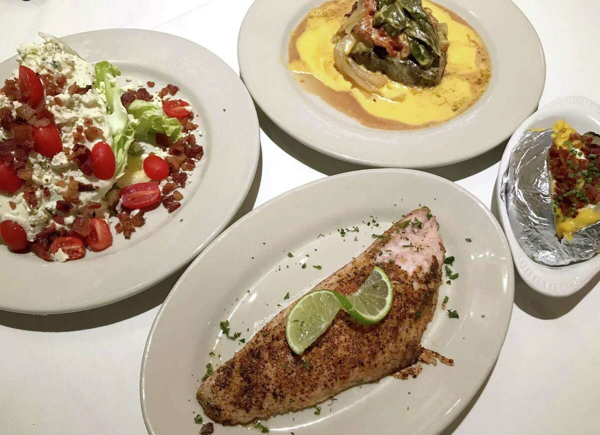 Wedge salad (clockwise from left), the House Special Steak, a loaded baked potato and grilled red snapper from Hoffman's Steakhouse