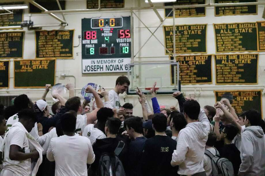 Notre Dame-West Haven manager Matt Callahan was carried off the court after hitting a 3-point on Senior Night Friday against Career. Photo: Contributed