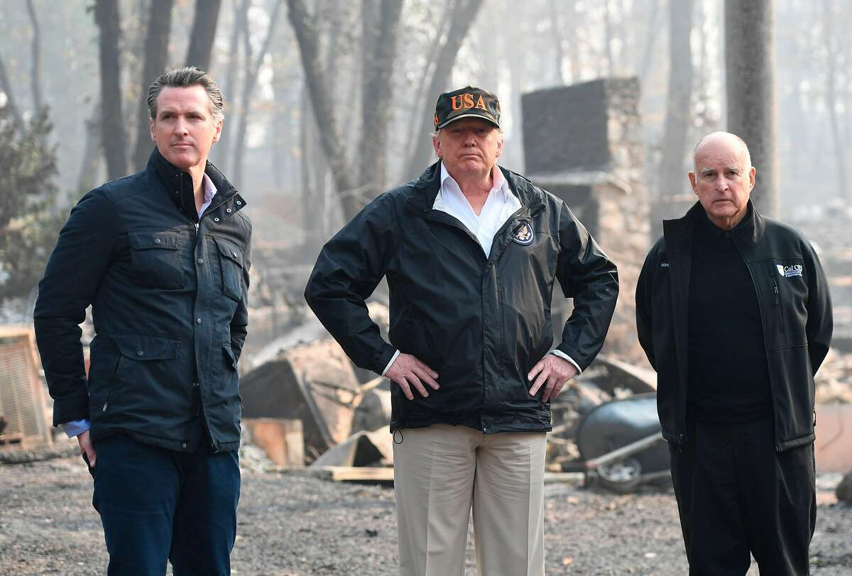 US President Donald Trump (C) looks on with Governor of California Jerry Brown (R) and Lieutenant Governor of California, Gavin Newsom, as they view damage from wildfires in Paradise, California on November 17, 2018. Newsom recently announced his intention to withdraw most of California's National Guard troops from the border, saying the state needs them to prepare for wildfires and to fight drug trafficking. (Photo credit should read SAUL LOEB/AFP/Getty Images)