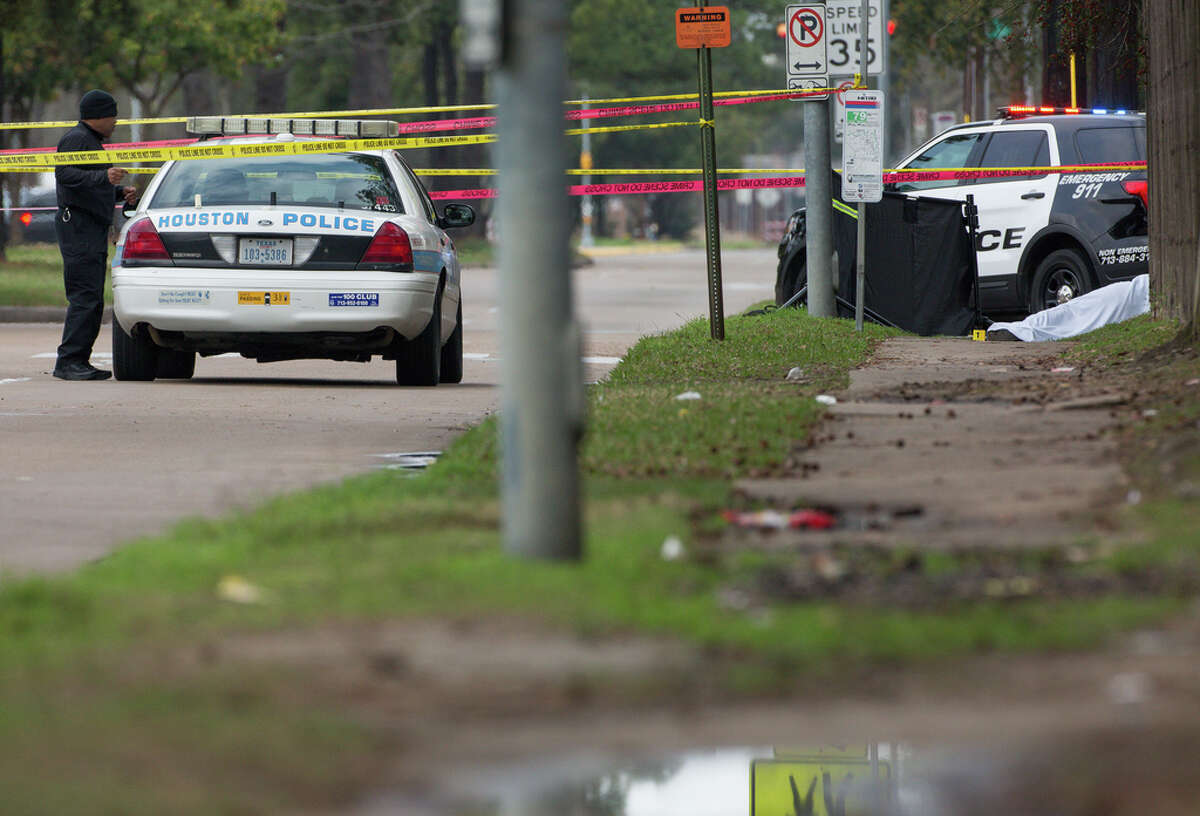 Authorities investigate the scene where a man was found dead on the corner of T.C. Jester Boulevard and Holder Forest Drive Monday, Feb. 11, 2019, in Houston.