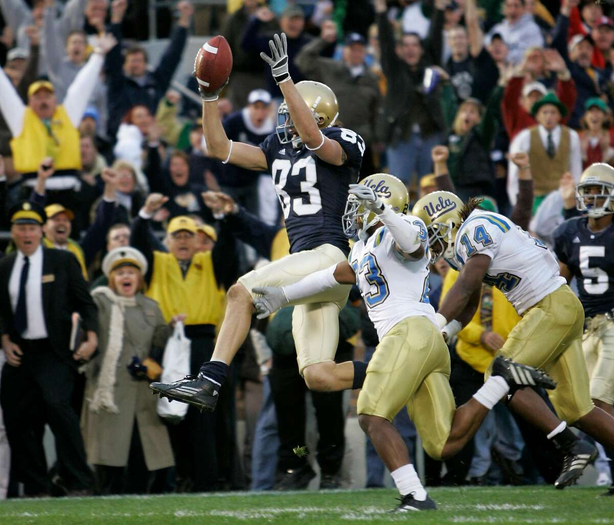 Notre Dame wide receiver Jeff Samardzija, center, leaps into the the end zone in front of UCLA cornerback Trey Brown, right center, and Chris Horton, right, to score the game-winning touchdown in the closing seconds of the game during college football action in South Bend, Ind., Saturday, Oct. 21, 2006. Notre Dames defeated UCLA 20-17. (AP Photo/Michael Conroy)