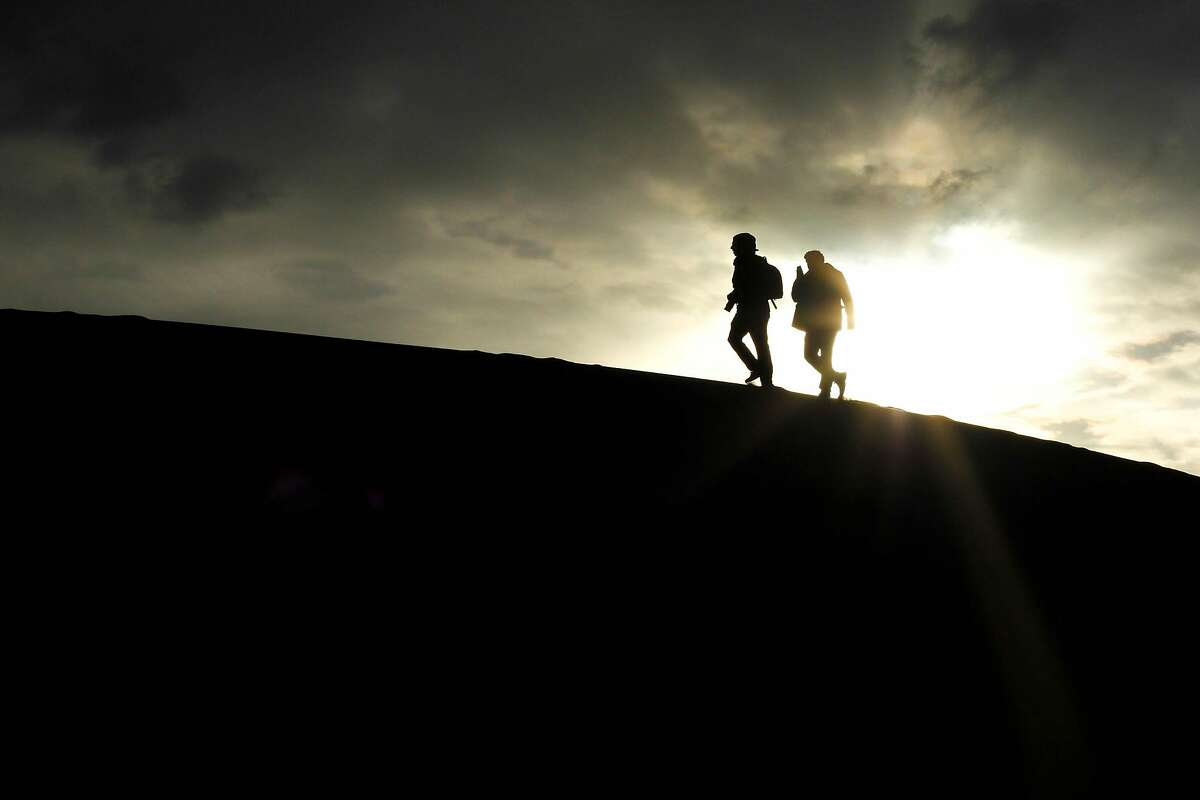 Two hikers walk along sand dunes in Death Valley National Park.