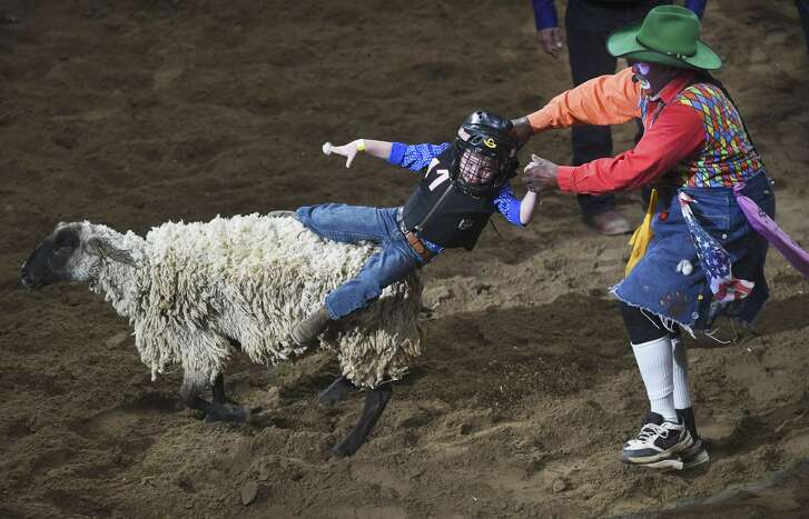 Garek Calvert is pulled off by rodeo clown Leon Coffee during the mutton busting event on opening night of the San Antonio Stock Show & Rodeo at the AT&T Center on Thursday, Feb. 7, 2019.