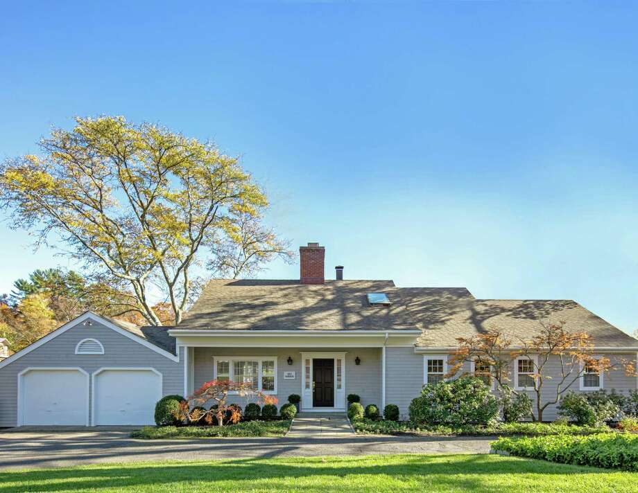 The gray colonial cottage at 163 Harbor Road sits on a third of an acre waterfront property in picturesque and historic Southport village.