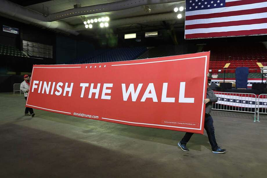 Workers carry a sign that reads 'Finish the Wall' as they prepare for the arrival of President Donald Trump for a rally at the El Paso County Coliseum on Monday, Feb. 11, 2019, in El Paso. Trump is expected to ask Congress to allocate funds for more wall to be built along the U.S./Mexico border as the Democrats in Congress ask for money for other border security measures. (Photo by Joe Raedle/Getty Images) Photo: Joe Raedle, Staff / Getty Images / 2019 Getty Images