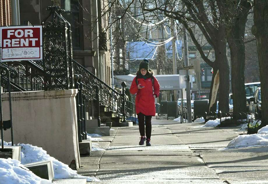A woman looks at her phone while walking down Willett St. on a cold day on Monday Feb. 11, 2019 in Albany, N.Y. (Lori Van Buren/Times Union) Photo: Lori Van Buren, Albany Times Union