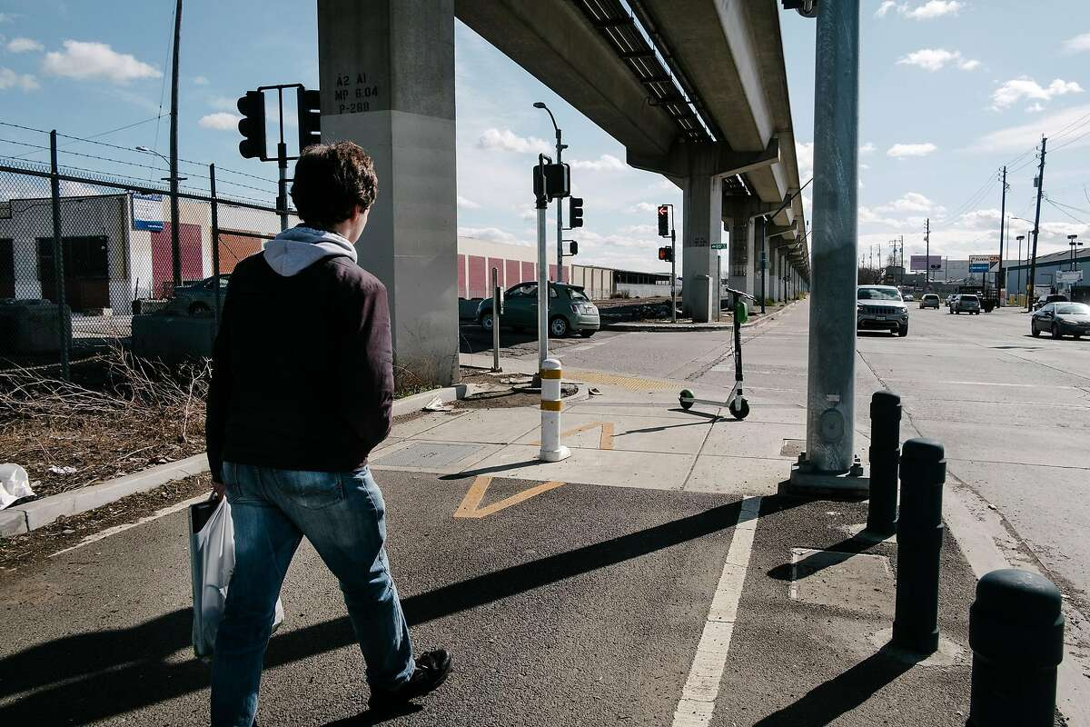 A person walks towards the corner of San Leandro and 85th Avenue where a designated bike and pedestrian lane ends, in Oakland, Calif., on Monday, February 11, 2019.