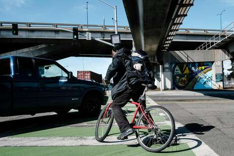 John Reed dodges a turning truck as he tries to cross 75th Avenue while riding along a designated bike path on San Leandro Street. Photo: Michael Short / Special To The Chronicle