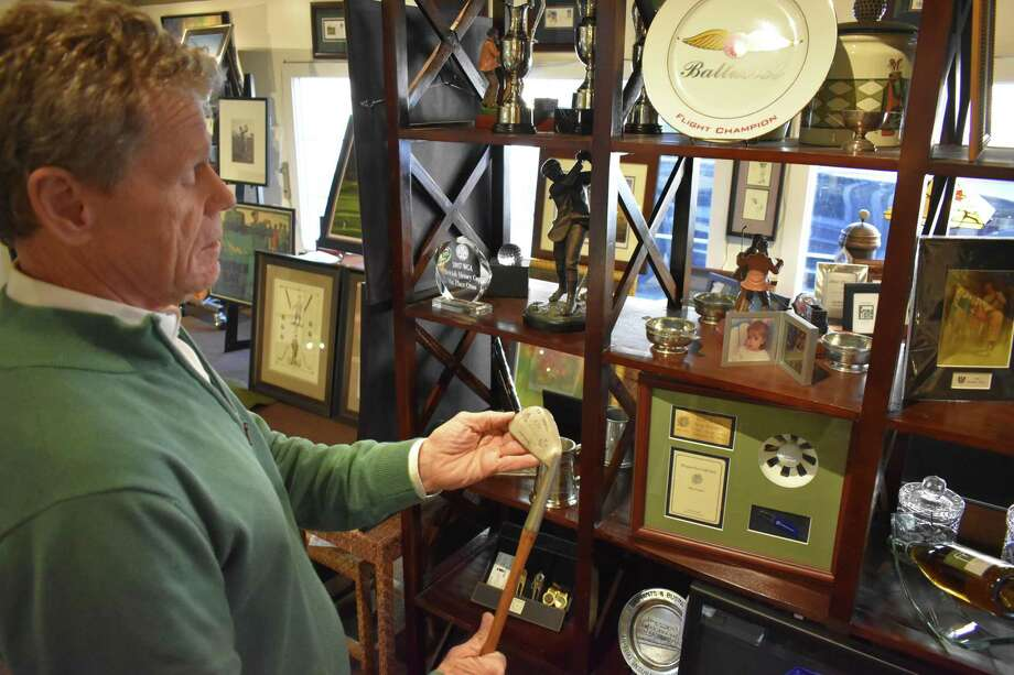 Golf Art owner Skip Rooney in February 2019 with a vintage golf club, part of an extensive collection for sale of prints and artifacts for sale at the Ridgefield, Conn. shop. Photo: Alexander Soule / Hearst Connecticut Media / Stamford Advocate
