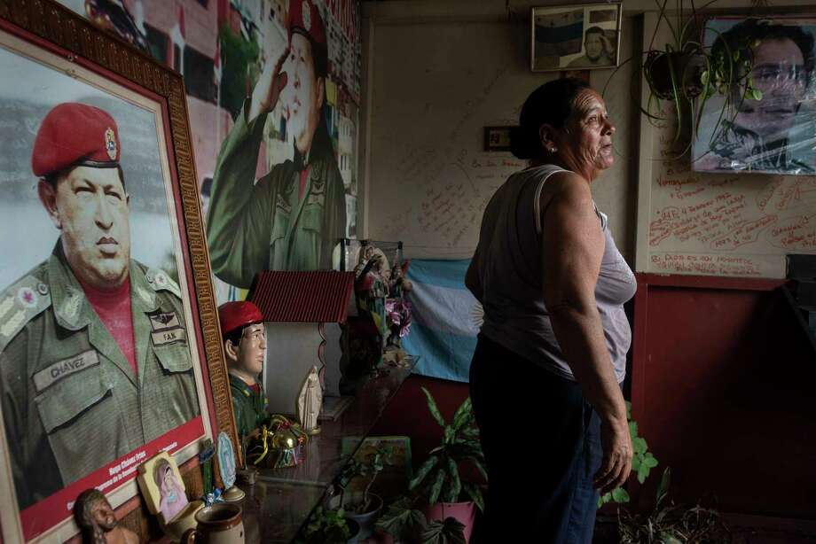 Elizabeth Torres, 54, takes care of a small shrine honoring the late Venezuelan President Hugo Chávez in Caracas on Feb. 8, 2019. Photo: Washington Post Photo By Michael Robinson Chavez. / The Washington Post